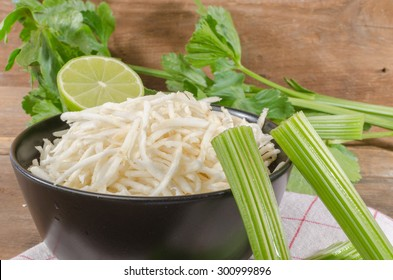 Bowl of grated celery on wooden background