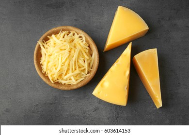 Bowl with grated cheese on dark background