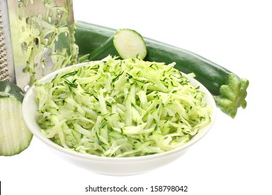 Bowl of grated zucchini on a white background