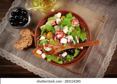 Bowl of Greek salad served on napkin on wooden background closeup