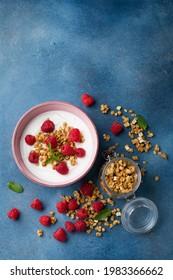 Bowl with greek yogurt, raspberries and granola. Top view flat lay. Healthy breakfast.