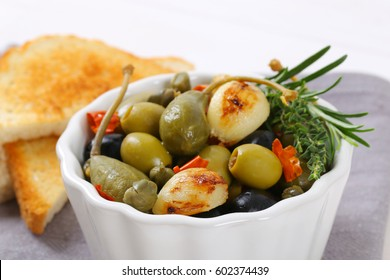bowl of green and black olives with garlic and toasts on grey place mat - close up