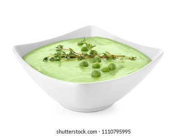 Bowl with green pea soup on white background