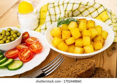 Bowl of green peas, slices of cucumbers, tomato cherry in plate, salt shaker, checkered napkin, white plate with cubes of fried potatoes, fork, slices of bread on wooden table