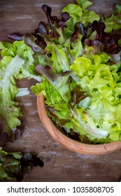 A bowl of green salad on the wooden table.  A bowl of green salad a day make good health benefits. Vegetables in salads are good sources of fiber. You can make a green salad at home in 5 minutes.