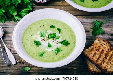 bowl of green zucchini cream soup with fresh parsley on wooden background
