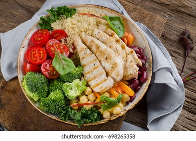 Bowl with grilled chicken, quinoa, chickpea, kale, broccoli and tomato. Healthy diet eating concept
