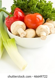 A bowl with group of fresh vegetables on white background.