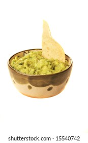 A bowl of guacamole with a chip