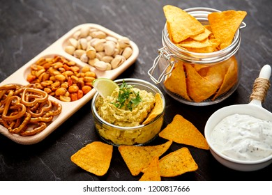 bowl of guacamole jar with nachos and salty snacks on an old black wooden table in a pub