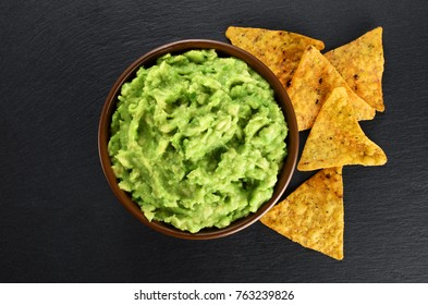 Bowl with guacamole and nachos on the background of a slate board. Top view.
