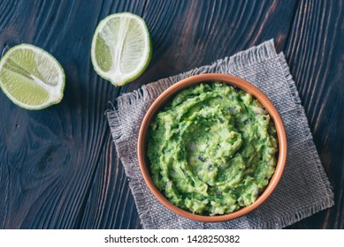 Bowl of guacamole on the wooden table close-up
