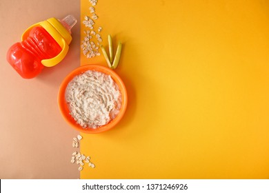 Bowl with healthy baby food and sippy cup on color background
