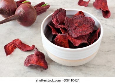 Bowl of healthy beet chips over a white marble background