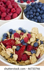 A bowl of healthy breakfast cereals served with strawberries, raspberries and blueberries bowls of which can be seen in the background.