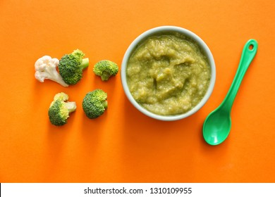 Bowl with healthy broccoli puree for baby on color background