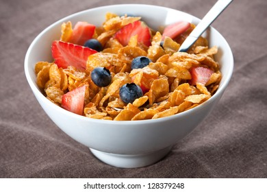 Bowl of healthy corn flakes breakfast cereal topped with fresh blackcurrants and strawberries served in a white ceramic bowl for a delicious meal