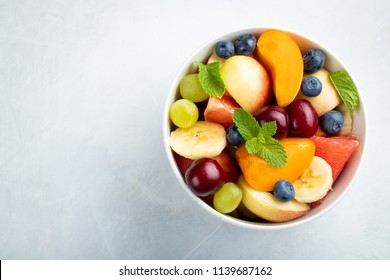 Bowl of healthy fresh fruit salad on a white background. Top view with copy space. Flat lay