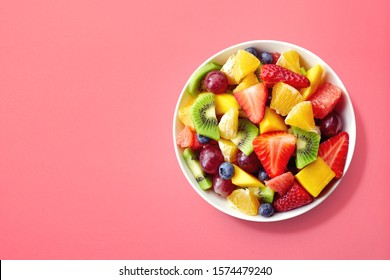 Bowl of healthy fresh fruit salad on pink background, top view - Shutterstock ID 1574479240