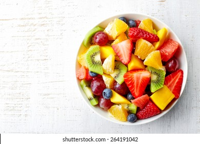 Bowl of healthy fresh fruit salad on wooden background. Top view. - Shutterstock ID 264191042
