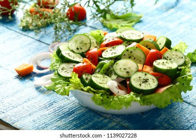 Bowl of healthy fresh mixed vegetable salad- vegan foods backgrounds.