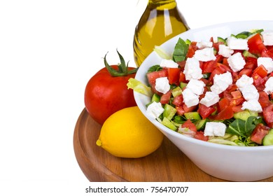 Bowl of healthy green salad with tomato and white cheese, served on wooden plate with vegetables and olive oil, isolated on white background.