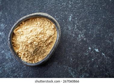 bowl of healthy maca powder on dark background