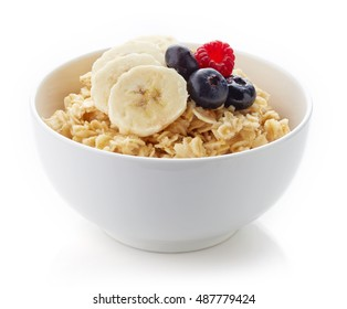 Bowl of healthy oatmeal with banana and fresh berries isolated on white background