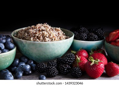 Bowl of healthy quinoa and fresh berries in green bowls, low key lighting and horizontal orientation