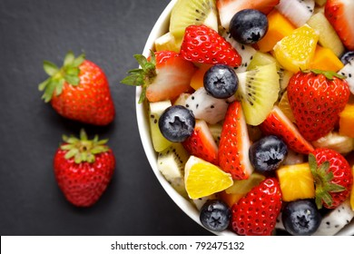 Bowl of healthy salad from fresh fruit on a dark table. Mixed fresh fruit (strawberries, orange, blueberries, kiwi, fruit, passion fruit).Healthy vegan lunch bowl, view from above.