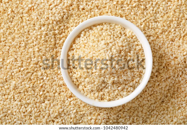 bowl of healthy sesame seeds on sesame seeds background