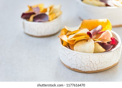 Bowl of Healthy Snack from Vegetable Chips, such as Sweet Potato, Beetroot, Carrot, Parsnip on Light Grey Background