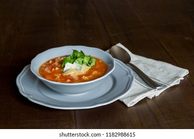 Bowl of healthy traditional tomato soup with rice on wooden table