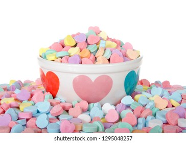 Bowl with hearts holding pile of candy hearts surrounded by pile of more candy isolated on white background. Traditional Valentine's Day candy.