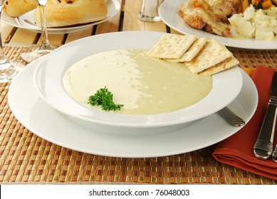 a bowl of hearty cream of broccoli soup with a chicken dinner in the background