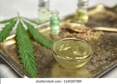 Bowl with hemp lotion on tray, closeup