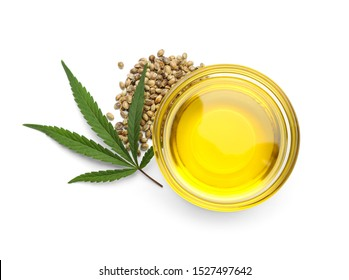 Bowl with hemp oil, leaf and seeds on white background, top view