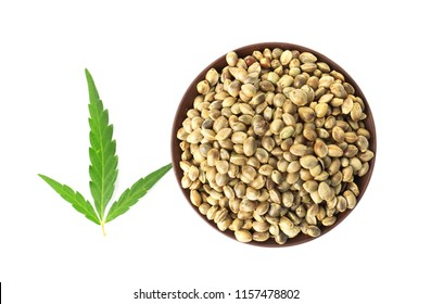 Bowl of hemp seeds with green leaf on white background, top view