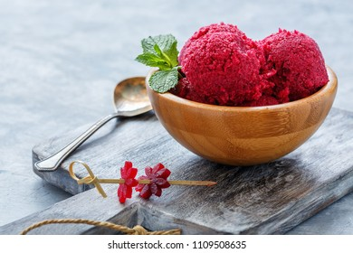 Bowl with homemade beetroot ice cream and mint sprig on a wooden serving board.