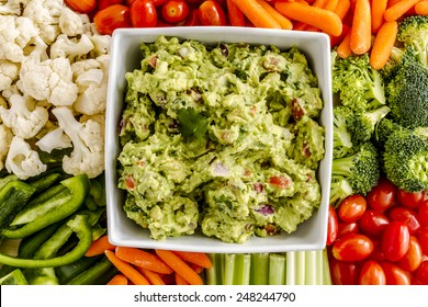 Bowl of homemade chunky guacamole surrounded by fresh vegetables