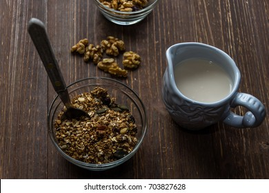 Bowl of a homemade granola breakfast with raisins and walnuts served with almond milk in a jug.