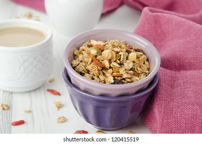 A bowl of homemade granola with goji berries on the table closeup