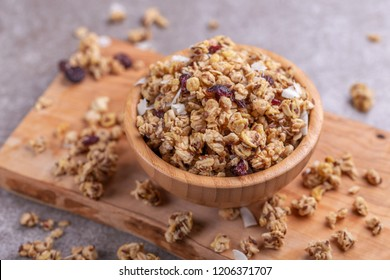 Bowl of homemade granola with nuts and raisins on grey slate background.  Top view. Copy space