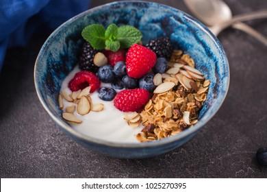 A bowl of homemade granola, yogurt, almond blossoms and fresh berries. vegetarian food concept