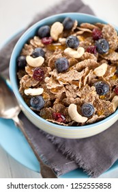 Bowl of homemade granola with yogurt and fresh berries on wooden background from top view.