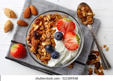 Bowl of homemade granola with yogurt and fresh berries from top view