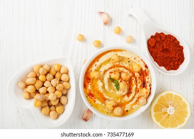 Bowl of homemade hummus on white wooden background , top view.