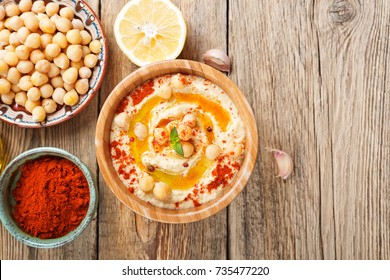Bowl of homemade hummus on wooden background , top view.