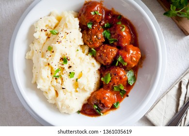 Bowl of homemade meatballs with mashed potatoes and tomato sauce