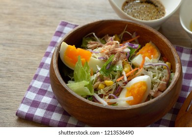 a bowl of homemade salad consists of tuna, boiled egg, cabbage, corn kennels with soy sauce sesame dressing